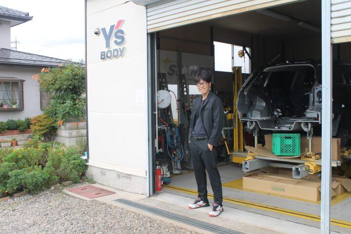 スーツ風作業着と自動車修理工場
